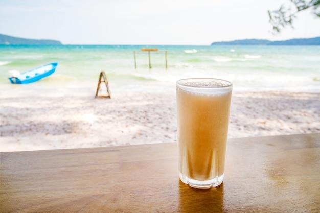 Mango orgânico fresco ou shake de laranja em restaurante tailandês na praia perto do mar, na ilha de koh phangan, tailândia. fechar-se. copo de suco gelado contra o mar azul-turquesa em um café-restaurante de rua