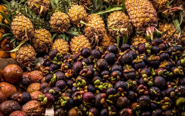 Mangostão e abacaxi no mercado de balcão na tailândia
