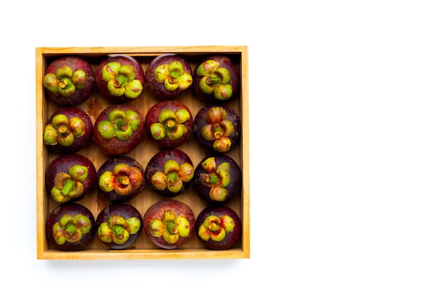Mangostão em caixa de madeira em fundo branco.