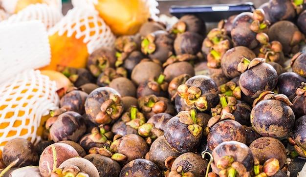 Mangostão fresco à venda em um mercado ao ar livre.