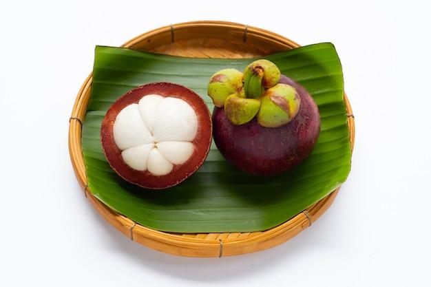 Mangostão na cesta de bambu em fundo branco.