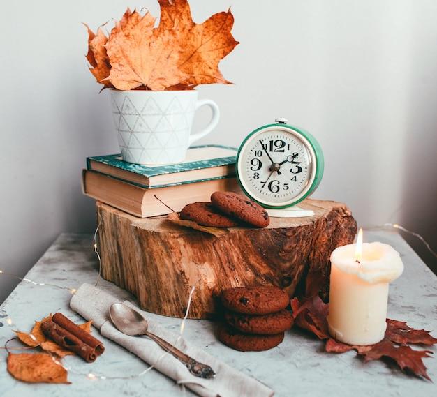 Manhã acolhedor com a xícara de café com creme e folhas de outono conceito do outono e do feriado.
