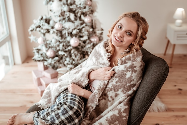 Manhã aconchegante. menina loira encantada sentada coberta por um cobertor de lã em uma poltrona espaçosa