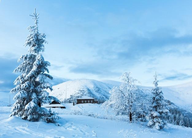 Manhã antes do nascer do sol, paisagem montanhosa de inverno com árvores cobertas de neve e uma casa na encosta