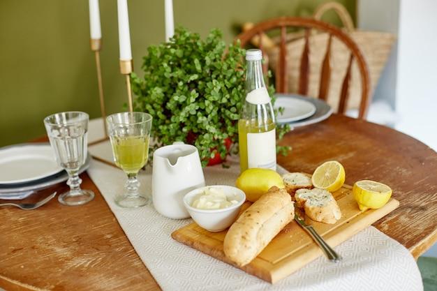 Manhã café da manhã pão com manteiga, limonada e limões. uma mulher espalha manteiga no pão