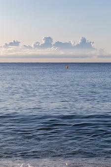 Manhã calma na praia vazia com um pneu de carro imprime na areia, com mar e nuvens ao fundo