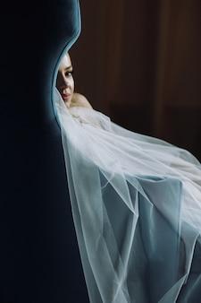 Manhã da noiva. noiva pensativa senta-se em uma cadeira azul profundo