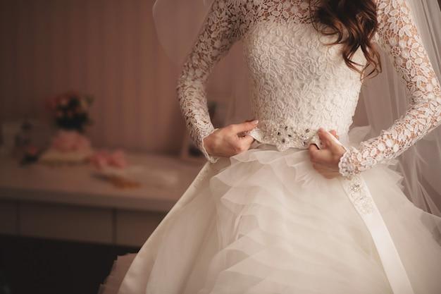 Manhã da noiva quando ela usa um lindo vestido, mulher se preparando antes do casamento