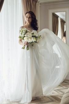 Manhã da noiva. uma linda mulher se prepara para um casamento, maquiagem natural e um penteado chique. peignoir branco e o vestido de noiva Foto Premium