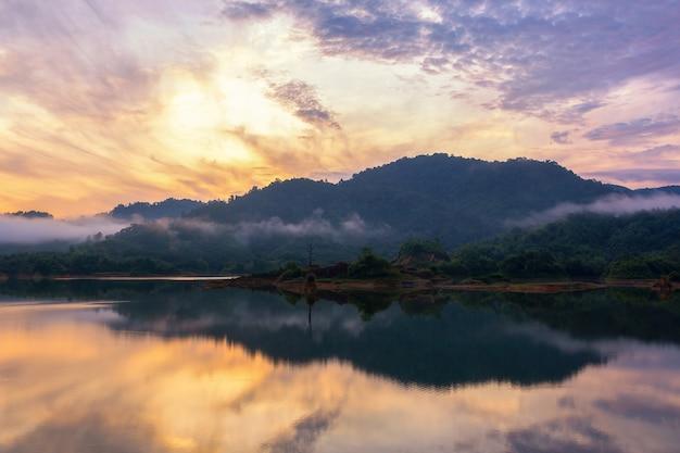 Manhã de bela paisagem com sol nascente no lago em hat som paen, distrito de mueang ranong, província de ranong, tailândia