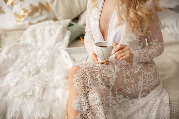 Manhã de casamento. mulher com uma xícara de café, modelo de boudoir, manhã de casamento da noiva linda