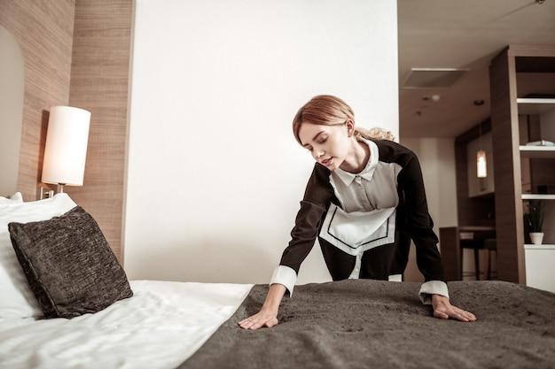 Manhã de governanta. jovem empregada loira e trabalhadora arrumando a cama pela manhã
