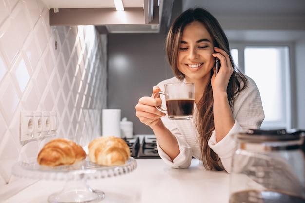 Manhã de mulher com telefone, croissant e café na cozinha