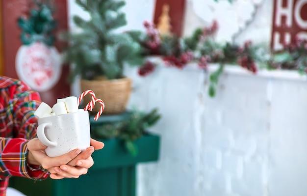 Manhã de natal, garota de pijama com uma xícara de chocolate quente com marshmallows. foco seletivo. feriado.
