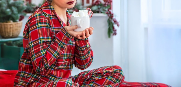 Manhã de natal, mulher de pijama com uma xícara de chocolate quente com marshmallows. foco seletivo.