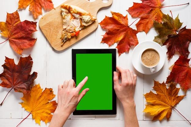 Manhã de outono de jovem contemporâneo portátil tablet pc café e pizza na mesa de madeira branca ...