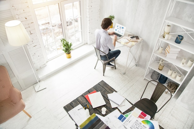 Manhã de trabalho. gerente profissional de cabelos escuros trabalhando em seu laptop enquanto está sentado à mesa