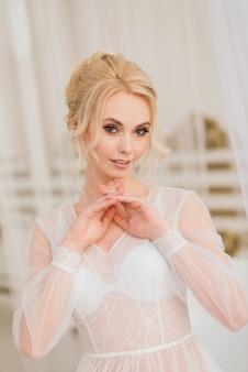 Manhã de uma jovem noiva linda em um vestido boudoir. estúdio, interior.