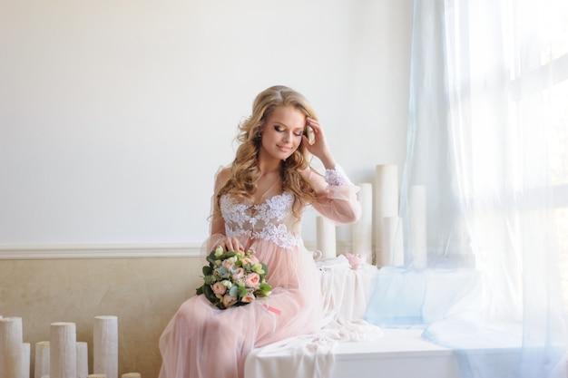 Manhã de uma jovem noiva linda em um vestido boudoir.