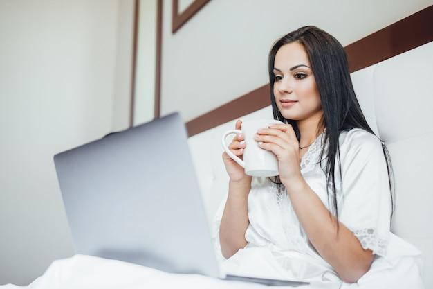 Manhã de uma linda garota com café e laptop