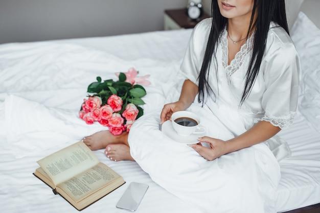 Manhã de uma linda menina com livro e rosas