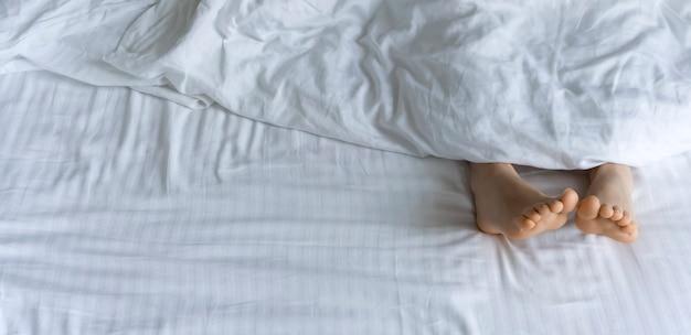 Manhã e acordar pés debaixo das cobertas na cama de manhã pés femininos debaixo das cobertas em uma cama branca relaxar sono descanso conceito foto de alta qualidade