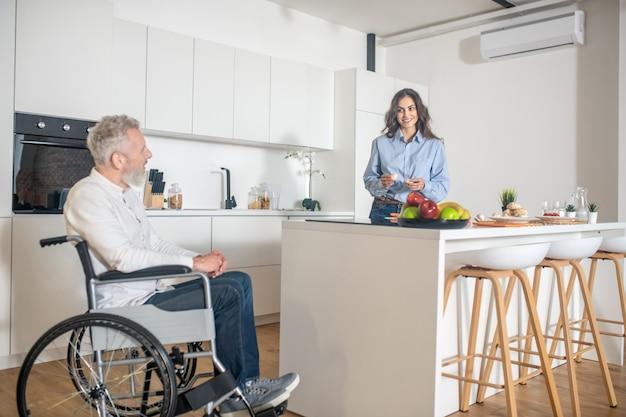 Manhã em casa. homem deficiente grisalho e esposa em casa antes do café da manhã