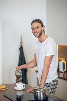 Manhã em casa. jovem em roupas de casa servindo café na xícara e sorrindo