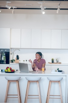 Manhã em casa. mulher jovem de pele escura tomando café da manhã em casa e assistindo algo em um laptop