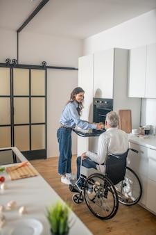 Manhã em família. jovem mulher de cabelos escuros preparando o café da manhã para o marido deficiente