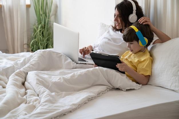 Manhã em família, no fim de semana, múmia trabalhando em um laptop deitada na cama com o filho da espera, tablet, jogar jogos