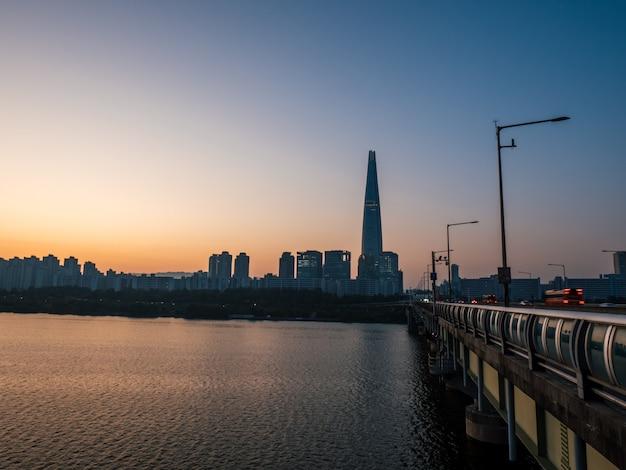 Manhã em seul, belo nascer do sol atrás de arranha-céus e torre.