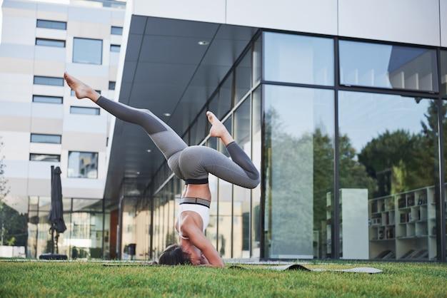 Manhã ensolarada de verão. mulher atlética nova que faz o pino na rua do parque da cidade entre edifícios urbanos modernos. exercício ao ar livre estilo de vida saudável