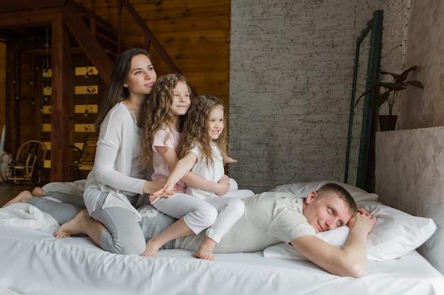 Manhã família as crianças com pais brincando na cama acordando de um sonho acabei de acordar amor