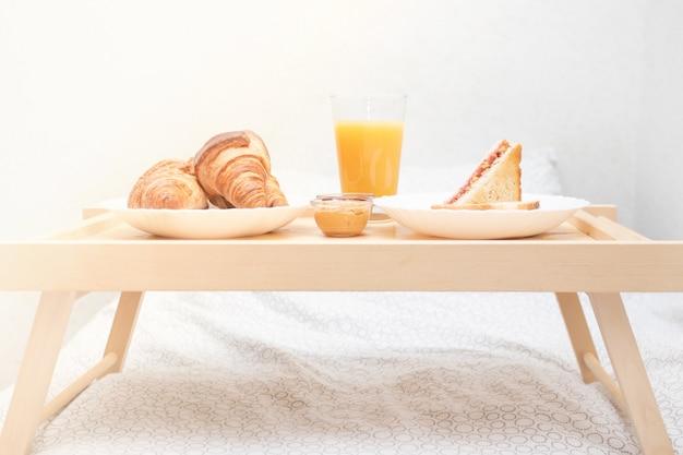 Manhã feliz. delicioso café da manhã na cama - croissants frescos, suco de laranja e manteiga de amendoim e sanduíche de geléia de framboesa.