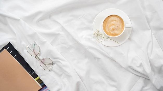 Manhã flatlay na cama branca. rotina de café e manhã. leia na cama.
