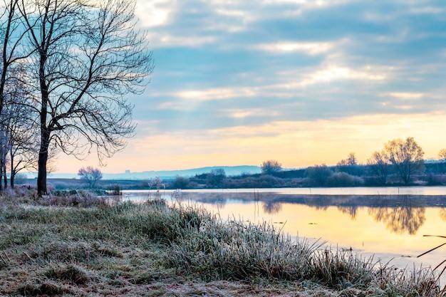 Manhã gelada à beira do rio, árvores cobertas de geada e grama perto do rio ao amanhecer
