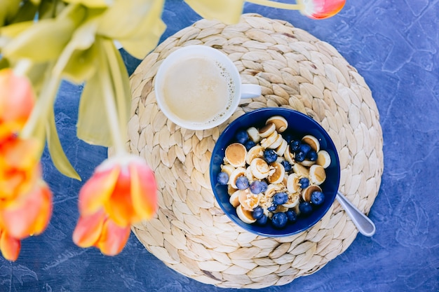 Manhã, hora do café da manhã, cereais mini pancake, mini panquecas em uma tigela azul escura com mel de xarope de bordo com mirtilo e xícara de café.