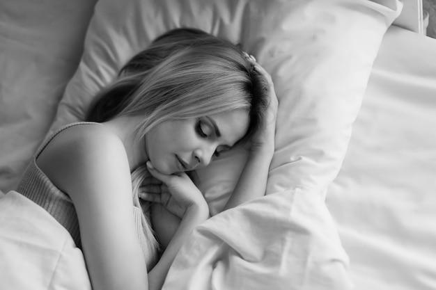 Manhã meninas: uma loira em um cobertor, sentada na cama. acordando de um sonho. acabou de acordar