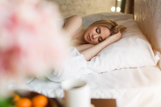 Manhã meninas: uma loira em um cobertor, sentada na cama. acordando de um sonho. acordei agora