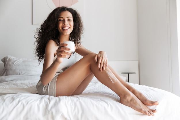 Manhã, mulher com cabelo comprido encaracolado sentada na cama com lençóis brancos limpos no quarto e aplicando creme corporal nas pernas
