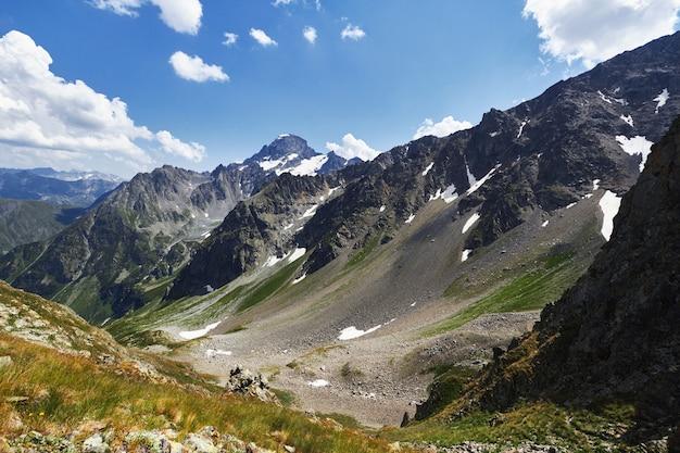 Manhã nas montanhas, uma fabulosa paisagem das montanhas do cáucaso. faça caminhadas escalando montanhas, picos e picos nevados. ar puro em uma manhã ensolarada entre as rochas