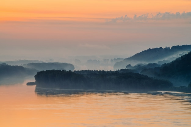 Manhã neblina mística acima amplo vale do rio. brilho de ouro do amanhecer no céu. margem do rio com a floresta sob o nevoeiro. luz solar refletida na água ao nascer do sol. paisagem atmosférica colorida de natureza majestosa.