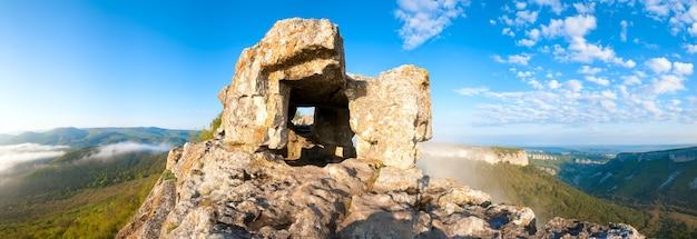 Manhã nublada vista de um dos quartos cavernícolas de mangup kale - fortaleza histórica e antigo assentamento de caverna na crimeia (ucrânia). imagem do ponto de sete tiros.