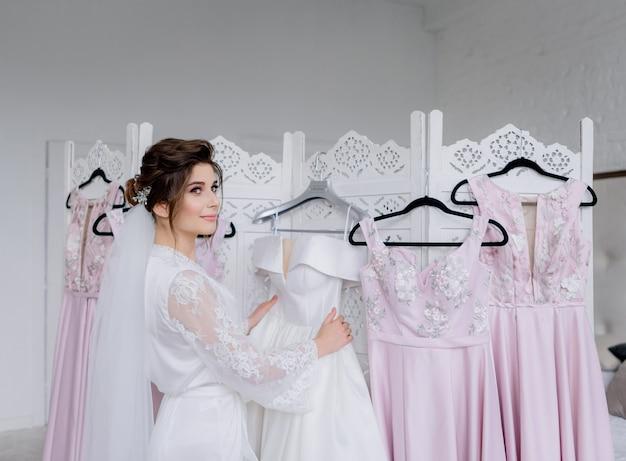 Manhã nupcial, linda noiva está se vestindo para a cerimônia de casamento, vestidos de noiva