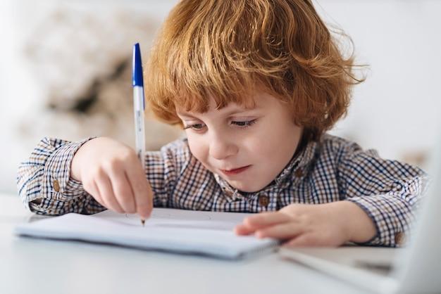 Manhã pensativa. rapaz charmoso ruivo motivado estudando em uma sala iluminada pelo sol enquanto faz anotações e está sentado à mesa branca