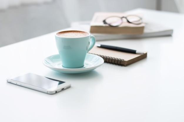 Manhã refrescante com o seu café favorito. smartphone, caderno e caneta na mesa