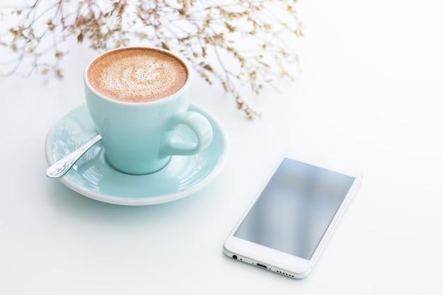 Manhã refrescante com o seu café favorito. smartphone e flor seca na mesa branca.