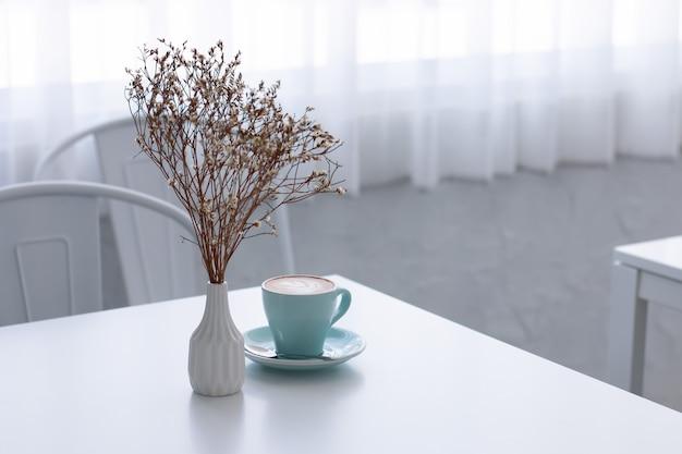 Manhã refrescante com o seu café favorito. vaso de flor seco na tabela na sala branca.