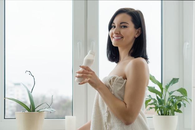Manhã, retrato, de, jovem, mulher sorridente, em, toalha banho, bebendo, leite, beba, iogurte, de, garrafa